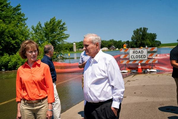 Gov. Mark Dayton and Sen. Tina Smith looked out Friday at County Road 38, cut off by the flooded Des Moines River in Currie, Minn.