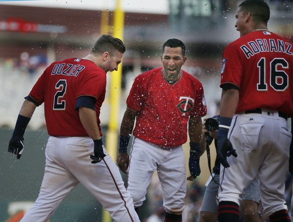Brian Dozier was greeted by Eddie Rosario and Ehrie Adrianza following his 10th-inning grand slam, which capped a 9-2 Twins homestand with an 11-7 vic