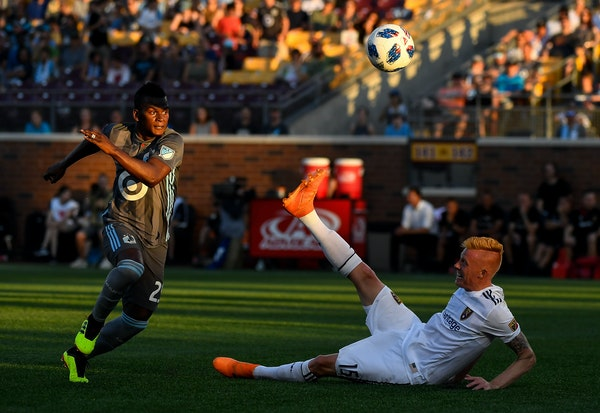 Real Salt Lake defender Justen Glad (15) falls to his back as Minnesota United forward Carlos Darwin Quintero (25) eyes the ball in the second half
