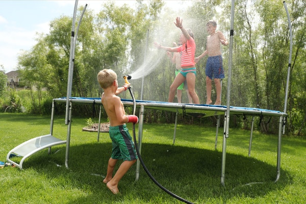 Rusty Golaski, center, 5, sprayed his siblings with a hose as they spent the afternoon playing with their friends on the family's trampoline, despite
