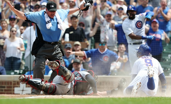 Much to the approval of the Cubs fans in the Wrigley Field stands Saturday, plate umpire Hunter Wendelstedt called Javier Baez safe at home plate as T