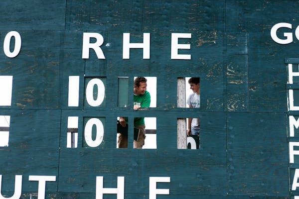 Milroy Irish manager Bob Dolan and his 14-year-old nephew Ezekiel Dolan replace numbers on the scoreboard at Irish Yard.