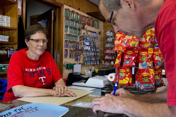 Eric Hexom signs the fishing license Joanne Rousseau provided him at Ebner's Live Bait in Elk River last July.