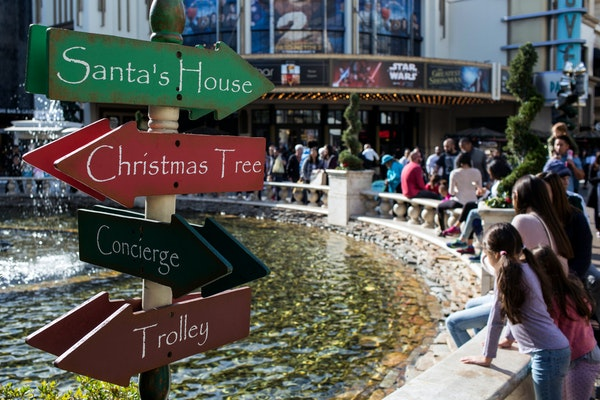 A directional sign is seen as shoppers sit around a fountain at The Grove in Los Angeles, on Dec. 22, 2017.