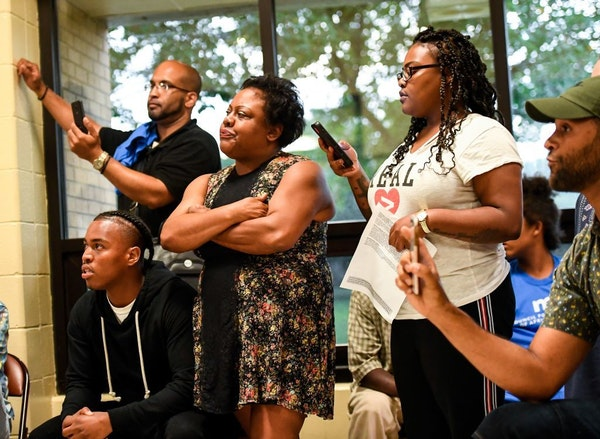 The Blevins family and angry community members listened as organizers of Thursday night's meeting tried to bring order back to the discussion.