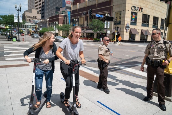 Sophie Konewko, left, and Megan Albers decided to take two Bird scooters for a ride through downtown Minneapolis after lunch Tuesday.