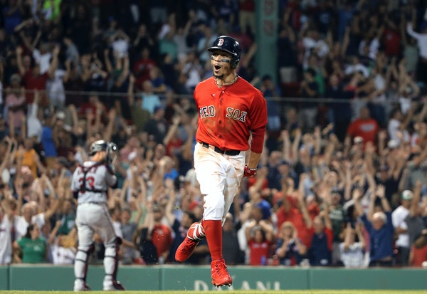Mookie Betts celebrates his walk-off solo home run as he rounds the bases in the 10th inning Frida at Fenway Park