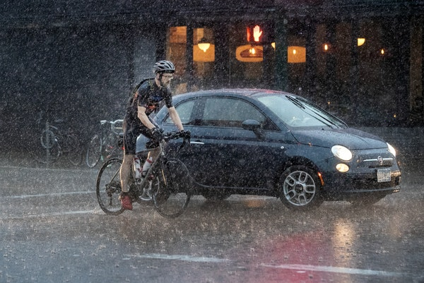 A cyclist crossed Lake Street in Minneapolis during a thunderstorm on Thursday.