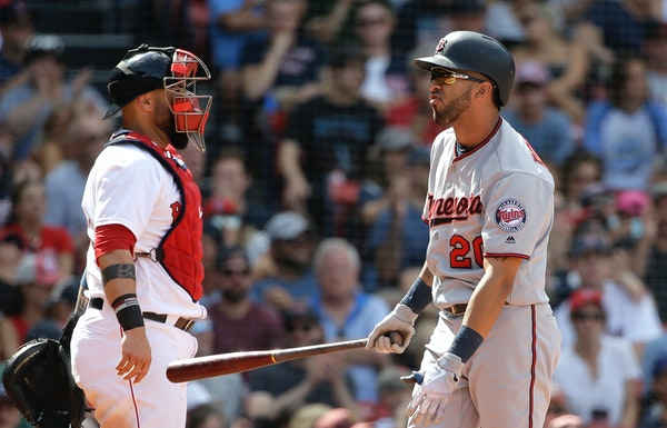 The Twins' Eddie Rosario, right, grimaced after striking out swinging as Red Sox catcher Sandy Leon looked on in the ninth inning Sunday at Fenway Par