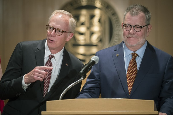 David McMillan Chair of the Board of Regents, left, and University of Minnesota President Eric Kaler took in a lighter moment after he announced to th