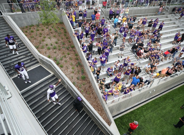 Minnesota Vikings wide receiver Stefon Diggs (14) waves to the fans as he enters the stadium at a night practice during the team's training camp at TC