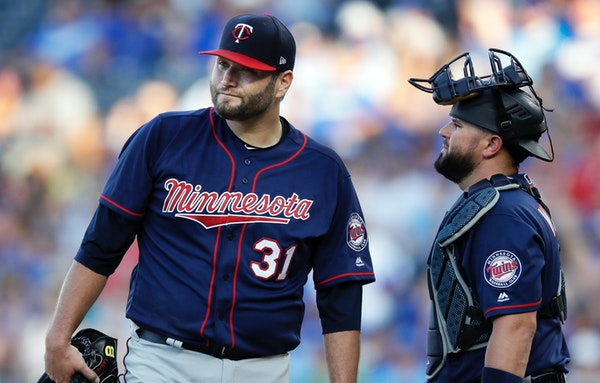 Twins starting pitcher Lance Lynn (31) and catcher Bobby Wilson, right, talk after the Kansas City Royals loaded the bases during the third inning