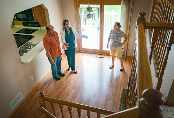 Real-estate agent Artemisa Boston, center, showed a Coon Rapids home to her clients on Wednesday.