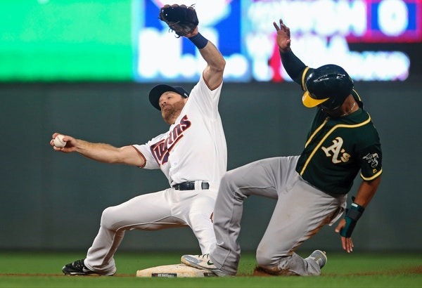 Oakland's Marcus Semien advanced to second on an infield hit as the Twins' Logan Forsythe tried to maintain his balance.