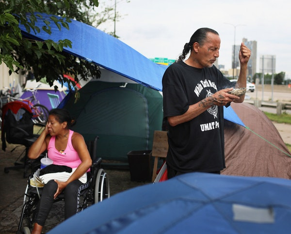 Yvonne, 32, sits in the makeshift camp just off of Hiawatha and Cedar Avenues as James Cross, founder of Natives Against Heroin, burns sage and prays