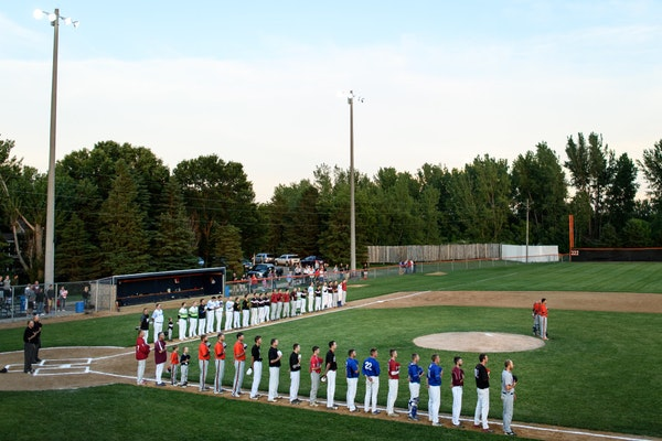 Players from the County Line League, back, and the Stearns County League held their hats over their hearts for the National Anthem before their all-st