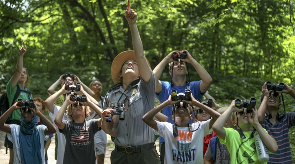 As part of their exposure to the great outdoors, kids used binoculars during a nature hike at Hidden Falls Regional Park.