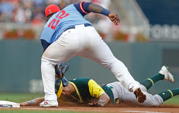 Oakland Athletics' Chad Pinder, bottom, is tagged out at third base by Minnesota Twins third baseman Miguel Sano