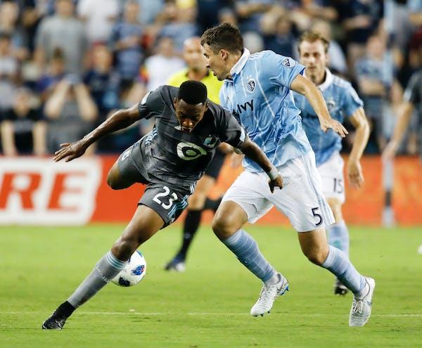 Minnesota United forward Mason Toye (23) loses control of the ball as Sporting Kansas City defender Matt Besler (5) defends