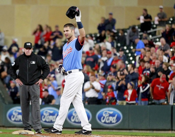 Minnesota Twins' Joe Mauer salutes the crowd after hitting a single against the Oakland Athletics in the fifth inning during a baseball game Friday, A