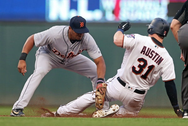 Tigers third baseman Jeimer Candelario, left, tags out Minnesota Twins' Tyler Austin in August
