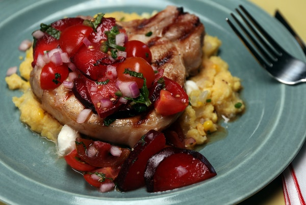 Whiskey-brined pork chops with tomato-plum relish served atop sweet corn and chive polenta.