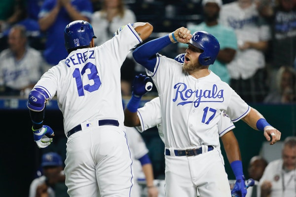 Kansas City Royals' Salvador Perez is congratulated at home plate by Hunter Dozier after hitting a two-run home run in the sixth inning