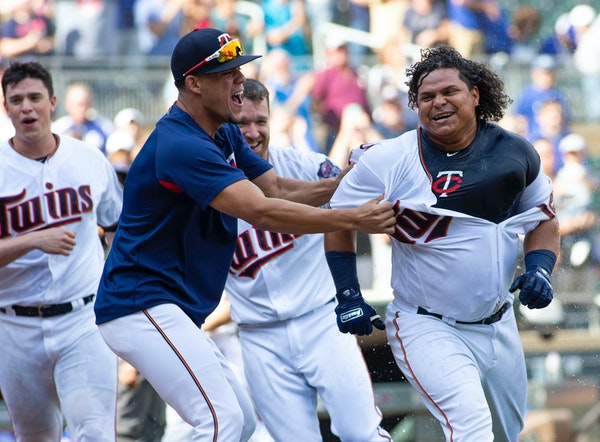Willians Astudillo, right, was mobbed by teammate Jose Berrios after hitting a two-run walk-off home run on Sept. 9.