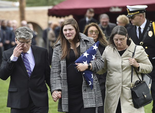 Andrea Parise, center, widow of corrections officer Joseph Parise, leaves his graveside services at Fairview Cemetery in Stillwater, Minn., on Tuesday