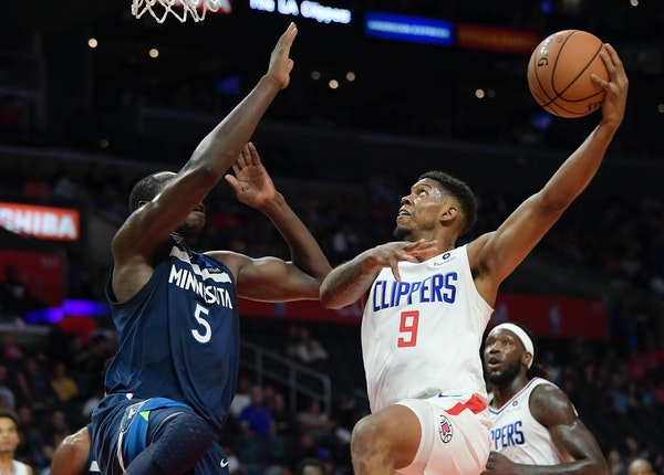 Los Angeles Clippers guard Tyrone Wallace, right, shoots as Timberwolves center Gorgui Dieng defends during the first half Wednesday night.