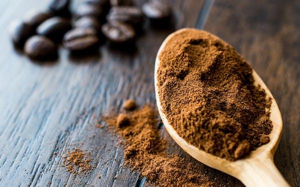 Instant espresso powder in wooden spoon.