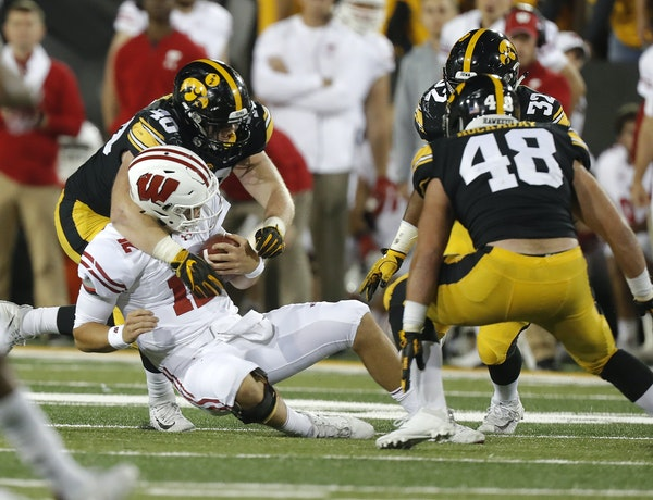 Iowa defensive end Parker Hesse, left, tackled Wisconsin quarterback Alex Hornibrook last month in Iowa City