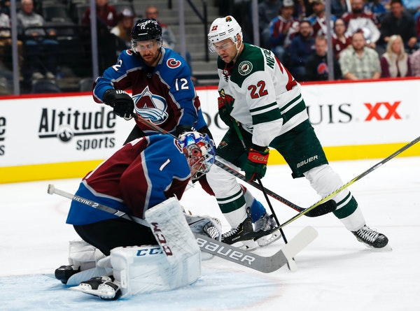 Colorado goaltender Semyon Varlamov stops a shot by Wild right wing Nino Niederreiter as Avalanche defenseman Patrik Nemeth watches during the second
