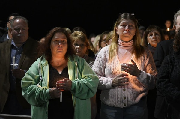 Maria Busch ,left, and Tammy Smith both of Amsterdam, N.Y., gather with family and friends for a candlelight vigil memorial at Mohawk Valley Gateway O