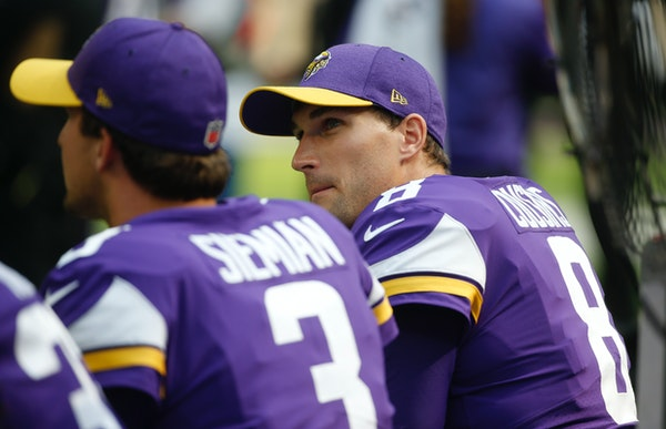 Minnesota Vikings quarterback Kirk Cousins, right, sits on the bench with teammate Trevor Siemian