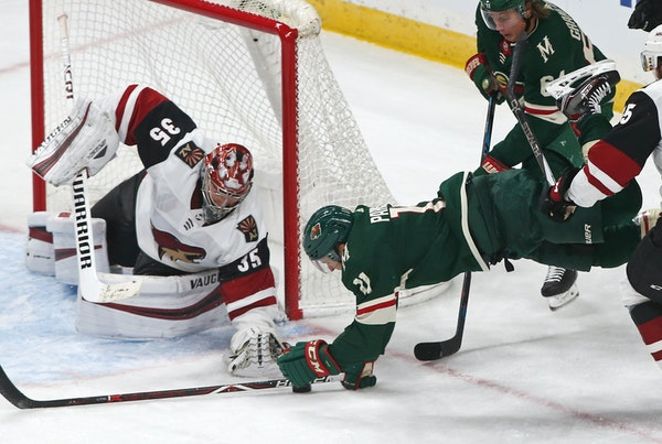 The Wild's Zach Parise, right, dives for the puck as Arizona goalie Darcy Kuemper reaches for it in the second period