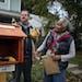 Todd Bol helped Eddye Watkins erect a Little Free Library on her yard in Minneapolis in October 2013.