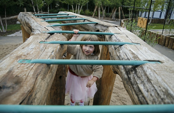 The outdoor play area at the U's Child Development Center features plenty of options, like these monkey bars tackled by Maren Vegoe on a recent fall