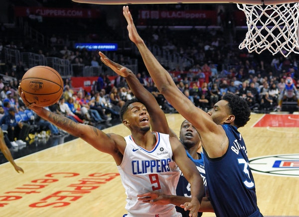 Clippers guard Tyrone Wallace, left, shoots as Timberwolves center Gorgui Dieng, center, and forward Keita Bates-Diop defend during the second half We