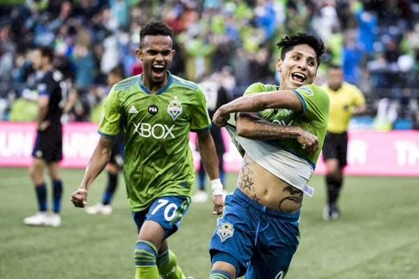 Seattle Sounders forwards Handwalla Bwana, left, and Raul Ruidiaz celebrate Ruidiaz' second goal during an MLS soccer match against the San Jose Earth