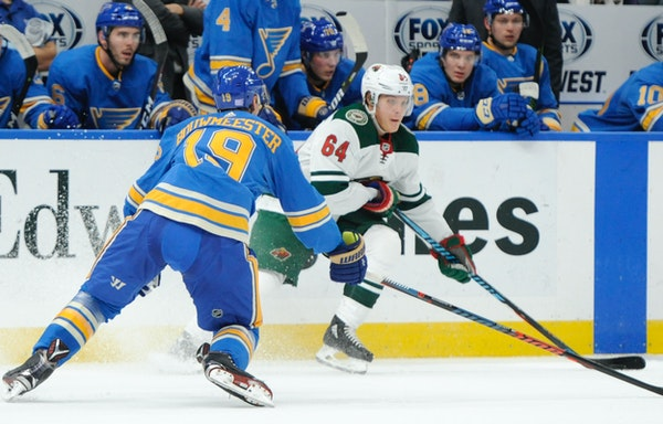 The Wild's Mikael Granlund looks to pass around St. Louis Blues' Jay Bouwmeester