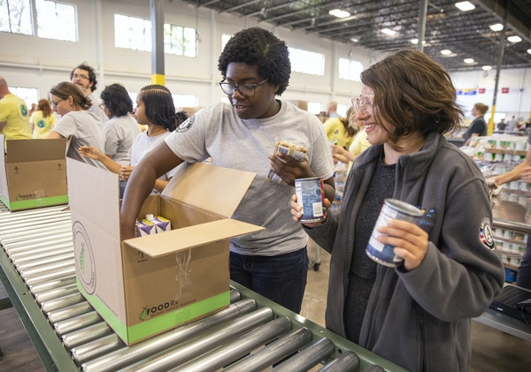 """Volunteers from Reading Partners helped pack FoodRx boxes. Boxes may vary to accommodate Somali and Hispanic preferences. """"People are looking forwar"""