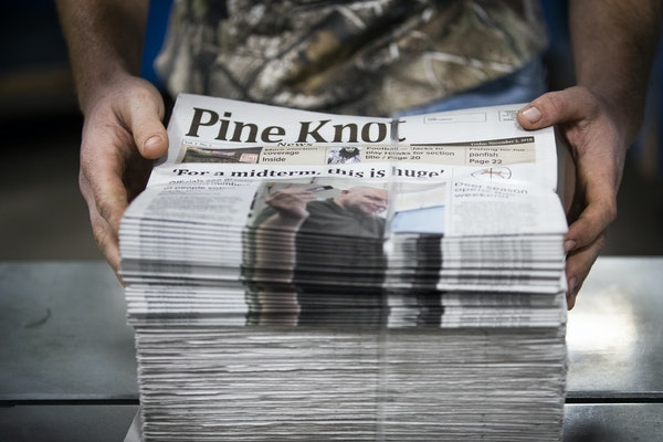 A mailroom associate at Star Printers in Cambridge stacks and binds freshly printed copies of the second issue of the Pine Knot News.