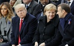 U.S President Donald Trump, second left, watches French President Emmanuel Macron putting his hand on German Chancellor Angela Merkel's knee during ce