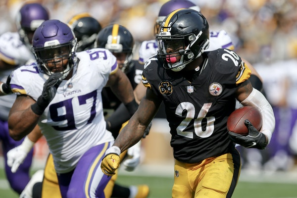 Pittsburgh Steelers running back Le'Veon Bell (26) tries to get away from Minnesota Vikings defensive end Everson Griffen (97) during an NFL footbal