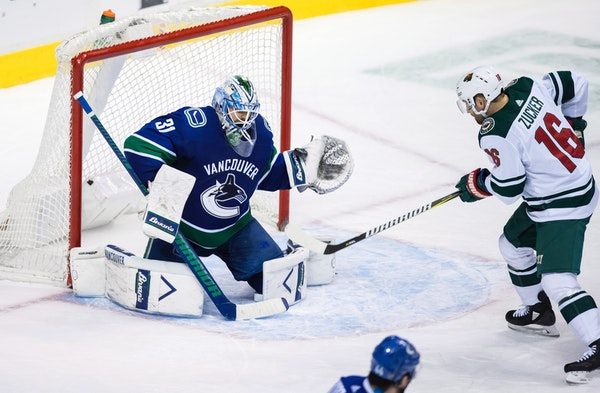 The Wild's Jason Zucker tips the puck past Vancouver goalie Anders Nilsson to score during the second period