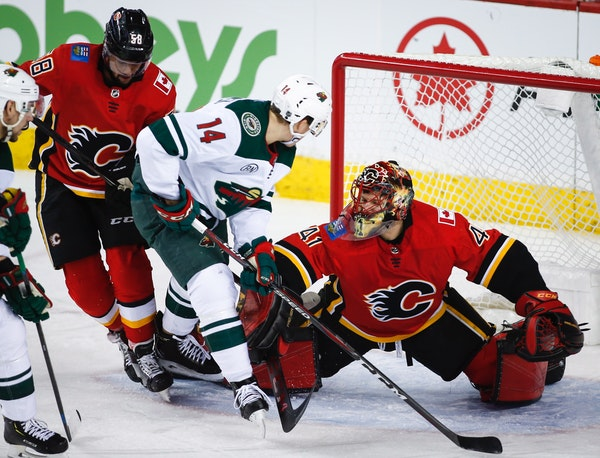 The Wild's Joel Eriksson, center, is shoved away from the net by Calgary Flames goalie Mike Smith as Oliver Kylington looks on
