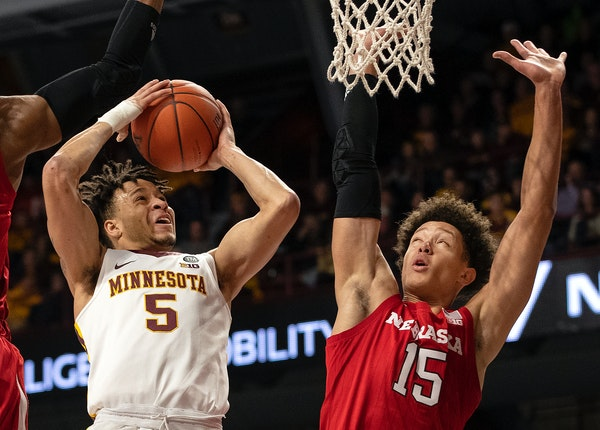 Amir Coffey is defended by Isaiah Roby in the first half