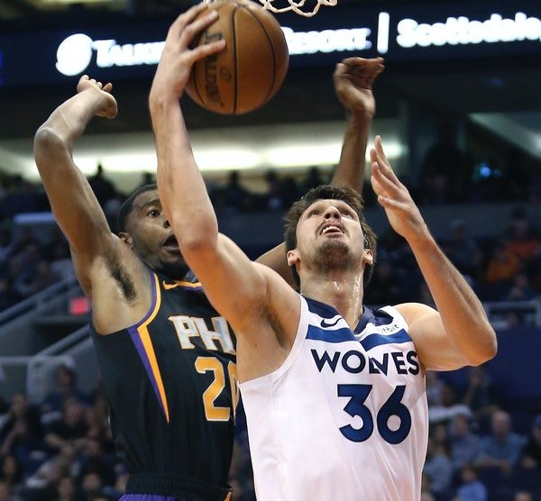 Timberwolves forward Dario Saric drives to the basket as the Suns' Josh Jackson defends during the first half