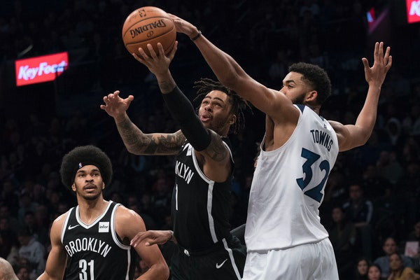 Brooklyn guard D'Angelo Russell (1) goes to the basket against Timberwolves center Karl-Anthony Towns on Friday.